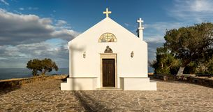 A small, modern, orthodox church. A small, white christian, orthodox church near the sea in the evening light Greece, island Crete Royalty Free Stock Photography