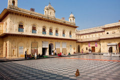 Small monkey and indian people sit in the white and black tiled courtyard Royalty Free Stock Photos