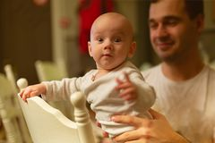 Small five month baby infant peeks out of the back of a chair in stock photos