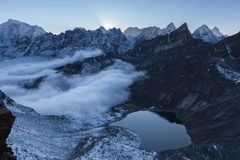 Small moraine lake and snowy mountain peaks in. Stock Photos