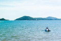 Small motor boat in blue sea heading out to open ocean royalty free stock photo