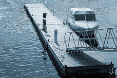 Small motor boat near floating wooden pier Royalty Free Stock Images