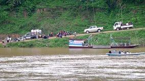 Small motor boat and people activity at the Mekong bank. Luang prabang, Laos - AUGUST 8, 2015: small motor boat with people across Mekong river and people stock video