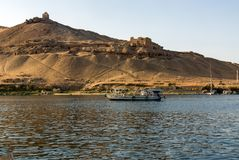 Small motor boat for tourists on the Nile River in Cairo Egypt, in the background ruins of an ancient Arab town in the desert. T. He tomb of the Aga Khan Royalty Free Stock Photography