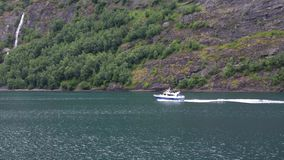 Small motor boat with tourists in Norway fjord. Small motor boat with tourists sailing at great speed along the Norwegian fjord. Tourism and travel. Mountains stock video footage