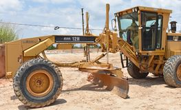 A small motor grader with GPS guidance system. A small motor grader with a GPS guidance system is shown on a construction site stock image