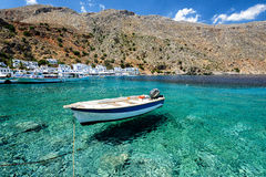 Small motorboat at clear water bay of Loutro town on Crete island, Greece.  royalty free stock photo