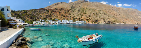 Small motorboat at clear water bay of Loutro town on Crete island, Greece Stock Photos