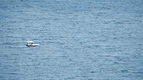 Small motorboat moving at sea. Distant small motorboat moving at sea royalty free stock photos