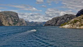 Small motorboat navigating into a fjord. Speedboat navigating into Lysefjord. Rogaland, Norway Stock Image