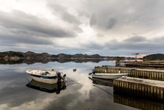 Forresfjorden, Karmoy in Norway - januray 10, 2018: A small motorboat resting in the water by a pier in the fjord Royalty Free Stock Photos