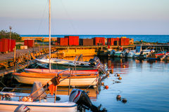 Small motorized boats laying in calm harbor at sunset Royalty Free Stock Photo