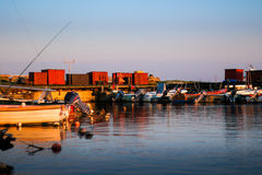Small motorized boats laying in calm harbor at sunset. Taken at the harbor of Boderne, on the island of Bornholm, Denmark. August 5, 2016 stock photography