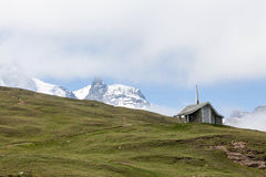 A small mountain chapel with snow mountain Stock Photography