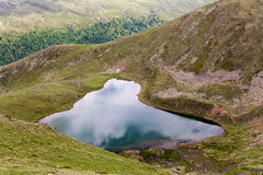 Small mountain lake Gruensee with green waters in Tyrol Alps Royalty Free Stock Photography