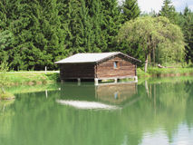Small mountain lake with house over water and forest background . Fie allo sciliar, South Tyrol, Italy Royalty Free Stock Images