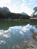 Small mountain lake with reflections of clouds Stock Photo
