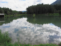 Small mountain lake with reflections of clouds Stock Photos