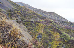 A small mountain road travels through the land of Alaska. Royalty Free Stock Images