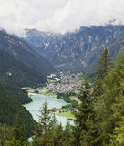 Small Mountain Town of Italy. The small mountain town of Auronzo in northern Italy nestled amongst the towering Dolomite Mountains beside the turquoise Lake Stock Photos