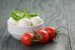 Small mozzarella balls in white bowl with plum Royalty Free Stock Images