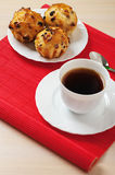 Small muffins on plate and cup. Of tea on red bamboo table cloth Stock Image