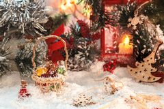 Small multi-colored glass bottles from Santa in a wicker basket with gifts on the background of a red lantern and New Year`s decor Royalty Free Stock Image