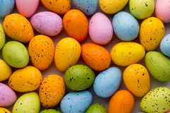 Small multicolored Easter eggs. Spring background. Stock Photos