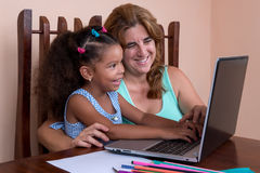 Small multiracial girl and her mother working on a laptop comput Royalty Free Stock Images