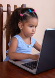Small multiracial girl working on a laptop computer Royalty Free Stock Images