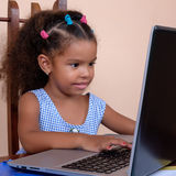 Small multiracial girl working on a laptop computer Stock Photo