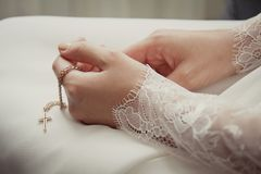 Small naive cross in the bride`s hands. Bride worries on her wedding day. Solitude before the wedding Royalty Free Stock Photo