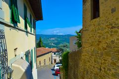 Small, narrow and colored street in Fiesole, Italy. With fields at background royalty free stock image