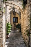 Small narrow street with ancient arches and walls in Rhodes town. Rhodes island., Greece Stock Photo