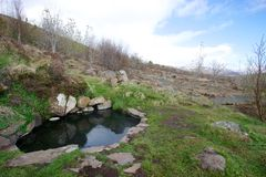 Small natural hot spring Krosslaug on hillside in Iceland. In West Iceland, a small natural hot spring (about 1.5 metres in diameter) called Krosslaug sits Stock Photos
