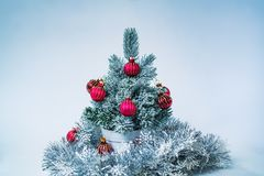 Small new year tree. Small decorated new year tree on white and blue background Stock Photo