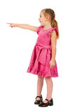 Small nice girl in pink dress pointing Stock Photography