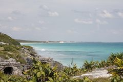 Niche and the sea of Tulum, Mexico. A small niche at the left, probably a tomb, are a nice change in the view of this splendid sea of tulum, with its blue royalty free stock photography