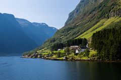 Small Norway village on the fjord bank. Peaceful scandinavian landscape with mountains. View from the water. Royalty Free Stock Photography