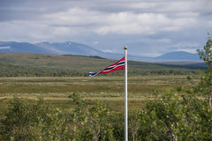 Small Norwegian flag with flat terrain behind Royalty Free Stock Images