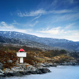 Small Norwegian lighthouse under blue sky Royalty Free Stock Photography