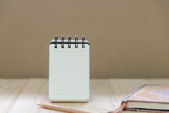 Small note book paper notepad stand for writing information with pencil and book. On wood table Stock Photos
