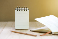 Small note book paper notepad stand for writing information with pencil and book. On wood table Royalty Free Stock Images