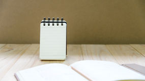 Small note book paper notepad stand for writing information with pencil and book. On wood table Royalty Free Stock Photo