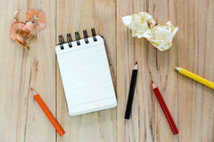 Small note book paper notepad for writing information with color pencil and crumpled paper balls on wooden table Royalty Free Stock Photos