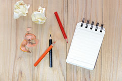Small note book paper notepad for writing information with color pencil and crumpled paper balls on wooden table Royalty Free Stock Images