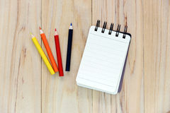 Small note book paper notepad for writing information with color pencil on wooden table. View from above Stock Photography