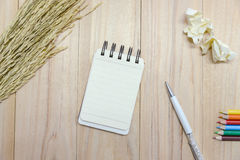 Small note book paper notepad for writing information with pen, color pencil and crumpled paper balls on wooden table Royalty Free Stock Images