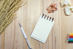 Small note book paper notepad for writing information with pen, color pencil and crumpled paper balls on wooden table. View from above Stock Photo