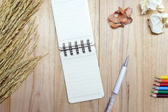 Small note book paper notepad for writing information with pen, color pencil and crumpled paper balls on wooden table. View from above Royalty Free Stock Photo